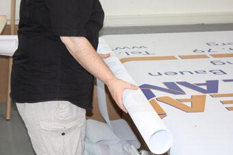 Ein Mitarbeiter von BANNERKÖNIG beim aufrollen eines Banners